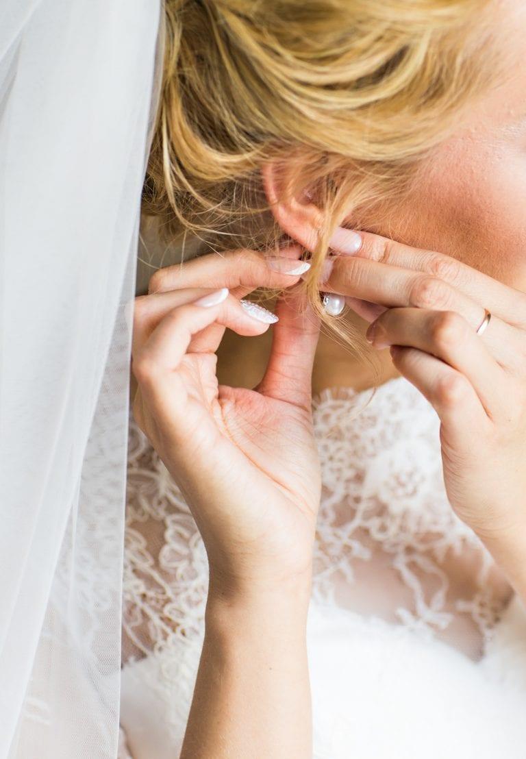 beautiful gorgeous bride putting on luxury earrings